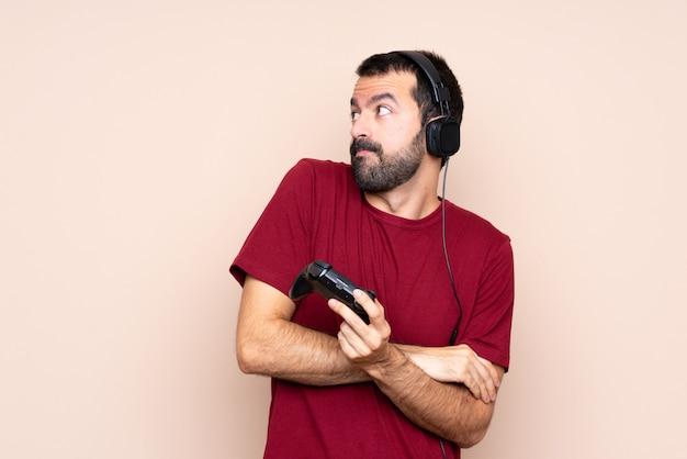 Equipaggi il gioco con un regolatore del videogioco sopra la parete isolata che fa il gesto di dubbi mentre sollevano le spalle