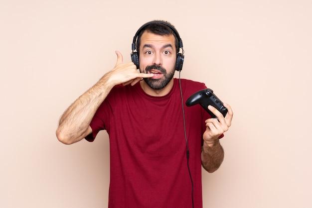Equipaggi il gioco con un regolatore del videogioco sopra la parete isolata che fa il gesto e il dubbio del telefono