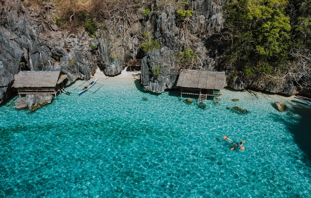 Equipaggi il kayak nella laguna gemella fra le rocce e le case dei pescatori, godendo del paesaggio. concetto di viaggi nelle filippine