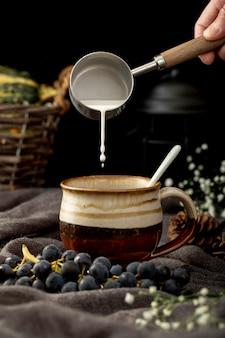 Equipaggi il latte di versamento in una tazza di caffè marrone con l'uva su un panno grigio