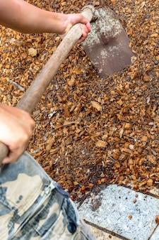 Equipaggi il lavoratore che usando l'attrezzatura della zappa sulla sporcizia dell'argilla del suolo