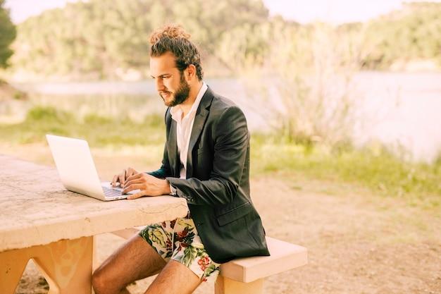 Equipaggi il lavoro con il computer portatile contro il paesaggio pittoresco