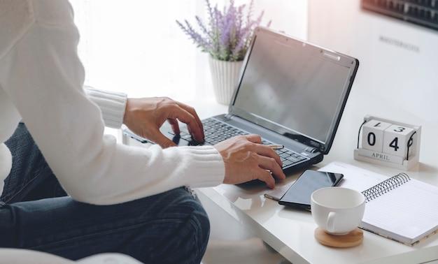 Equipaggi il lavoro con il computer portatile mentre si siedono nel salone a casa, lavorando dal concetto domestico.