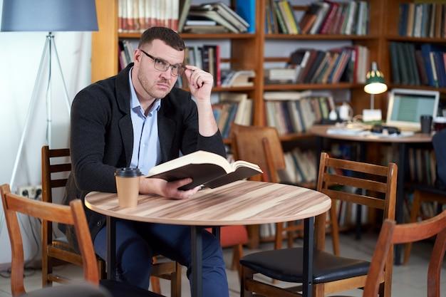 Equipaggi il libro di lettura e il caffè bevente in un caffè delle biblioteche con molti libri
