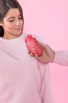 Equipaggi il modello del cuore della tenuta vicino alla giovane donna