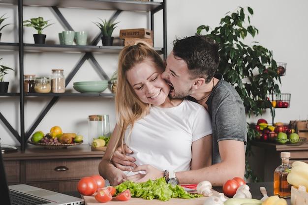 Equipaggi il mordere sulle guance della donna che stanno dietro il contatore di cucina con le verdure