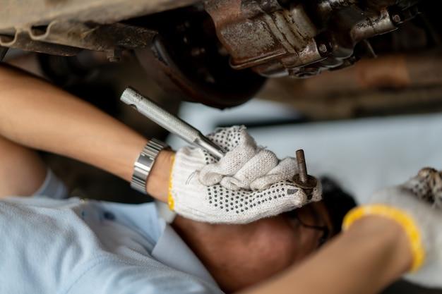 Equipaggi il motore di riparazione e manutenzione della vecchia automobile. concetto di guida sicura e cura dell'automobile.