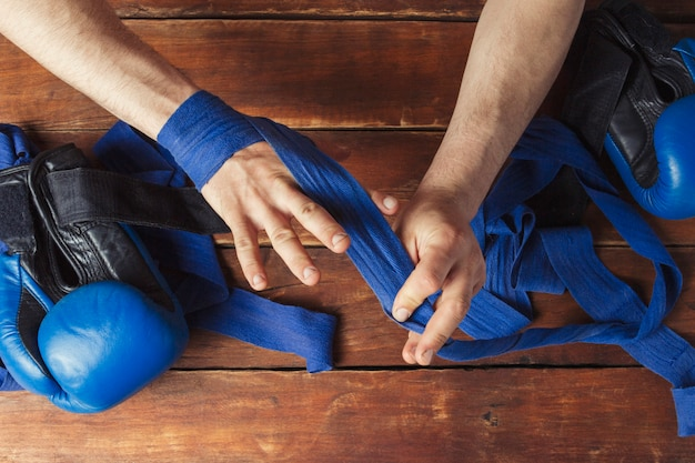 Equipaggi il nastro di pugilato della fasciatura sulle sue mani prima della partita di pugilato su una superficie di legno. il concetto di allenamento per la boxe o il combattimento. vista piana, vista dall'alto