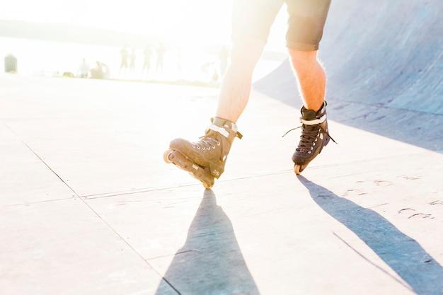 Equipaggi il pattinaggio a rotelle nel parco del pattino durante il giorno soleggiato