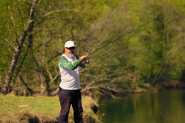 Equipaggi il pesce con la filatura sulla sponda del fiume, lanciando l'esca. attività nei fine settimana all'aperto. foto con profondità di campo ridotta a tutta apertura.