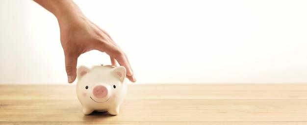 Equipaggi il porcellino salvadanaio della tenuta della mano sulla tavola di legno un denaro di risparmio per il concetto futuro di investimento.