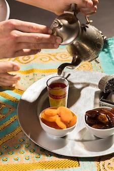 Equipaggi il tè di versamento nell'alta vista della tazza minuscola