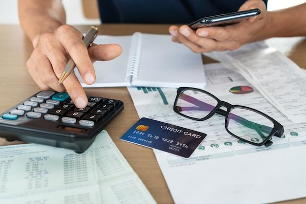 Equipaggi il telefono cellulare della tenuta e usando il calcolatore, il conto e il concetto di risparmio.