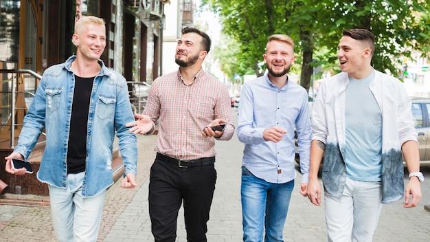 Equipaggi il telefono cellulare della tenuta in sua mano che gode con il suo amico sulla via