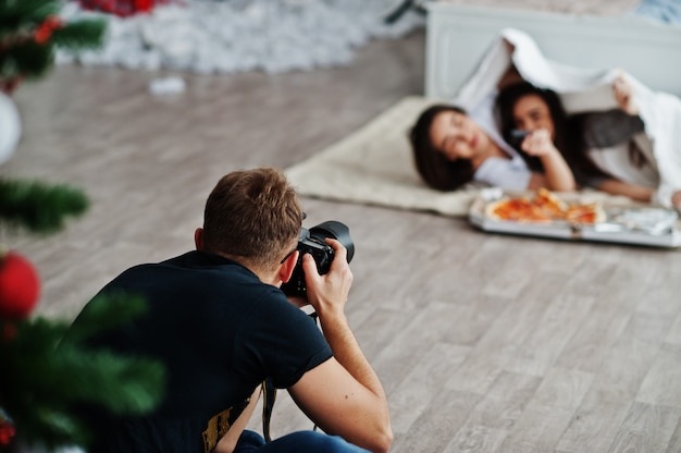 Equipaggi il tiro del fotografo sulle ragazze dei gemelli dello studio che stanno mangiando la pizza. fotografo professionista al lavoro.