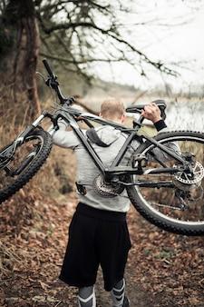 Equipaggi il trasporto della bici di sport sulla sua parte posteriore che cammina nella foresta