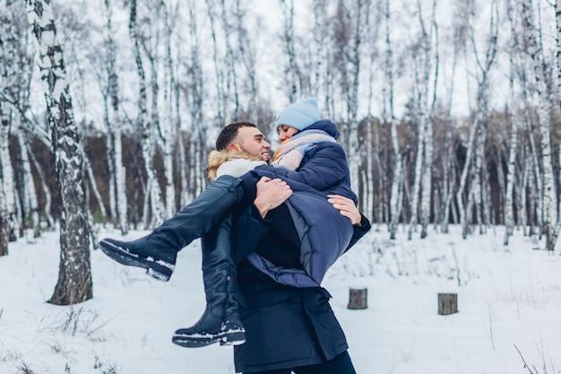 Equipaggi il trasporto della sua amica sulle mani nella foresta dell'inverno. le persone si divertono all'aperto. coppia rilassante