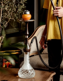 Equipaggi il tubo del narghilé della tenuta disposto sul tavolino da salotto