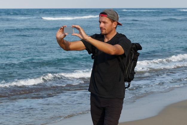Equipaggi il turista con lo zaino facendo uso del telefono cellulare per scattare la foto, stante su una spiaggia.