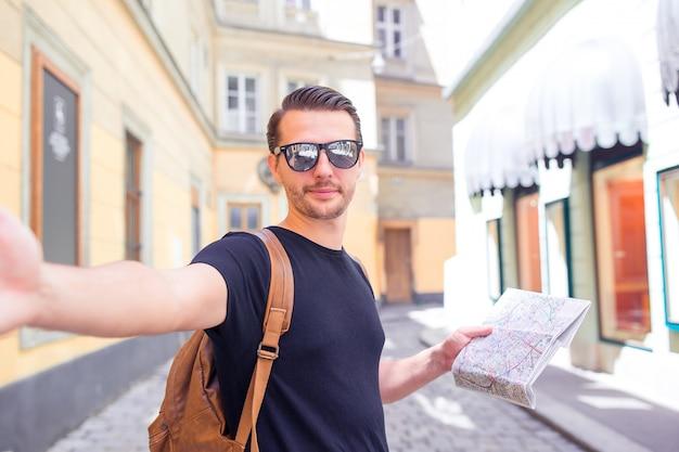 Equipaggi il turista con una mappa della città e lo zaino in via dell'europa. ragazzo caucasico che guarda con la mappa della città europea.