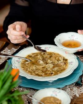 Equipaggi il versamento dell'aceto nella minestra della polpetta con le tagliatelle