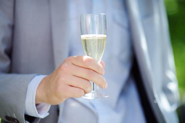 Equipaggi il vetro della tenuta con champagne, metta a fuoco sul vetro
