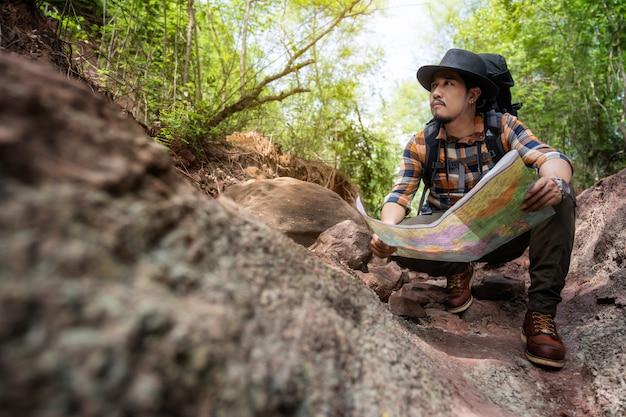 Equipaggi il viaggiatore con la mappa di seduta e della lettura dello zaino nella foresta