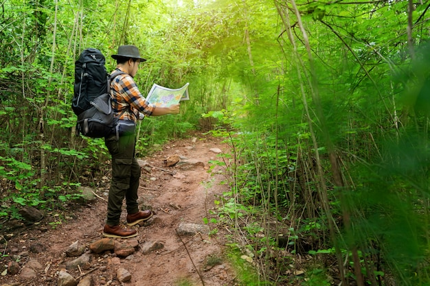 Equipaggi il viaggiatore con lo zaino e la mappa che cercano le direzioni nella foresta