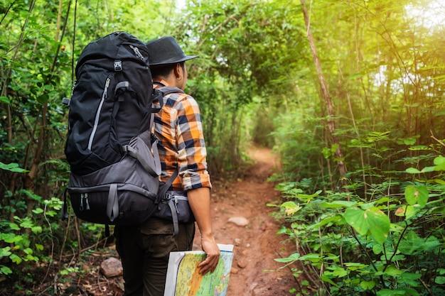 Equipaggi il viaggiatore con lo zaino e la mappa nella foresta
