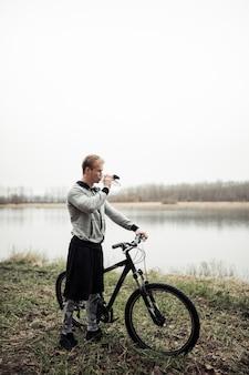 Equipaggi l'acqua potabile dalla bottiglia che si leva in piedi con la bicicletta vicino allo stagno