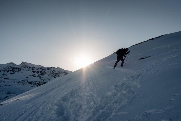 Equipaggi l'alpinista che scala sulla montagna nevosa nell'inverno al tramonto