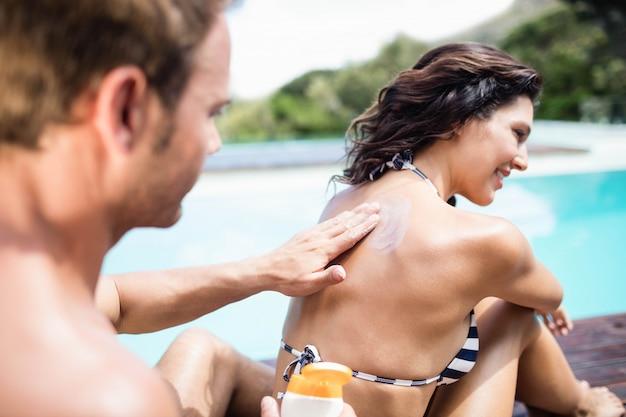 Equipaggi l'applicazione della protezione solare sulla parte posteriore della sua donna vicino allo stagno un giorno soleggiato