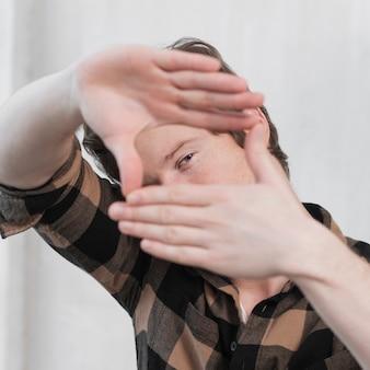 Equipaggi l'artista che fa una struttura con il suo primo piano delle dita