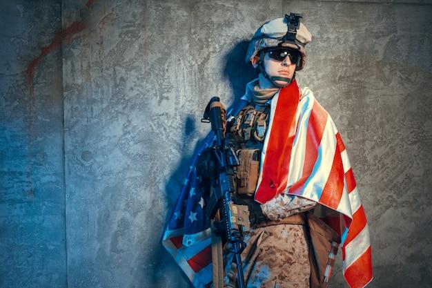 Equipaggi l'attrezzatura militare un soldato mercenario nei tempi moderni con la bandiera degli stati uniti in studio