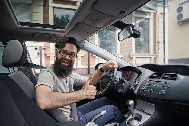 Equipaggi l'autista sorridente felice che mostra i pollici su che conducono l'automobile sportiva