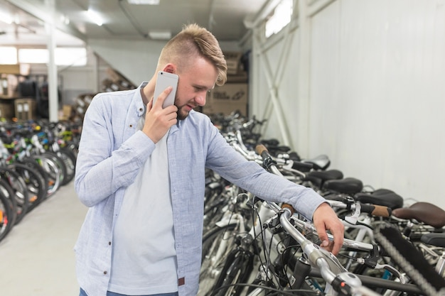 Equipaggi l'esame della bicicletta mentre parlano sul cellulare in negozio