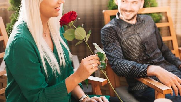 Equipaggi l'esame della donna che tiene la bella rosa rossa