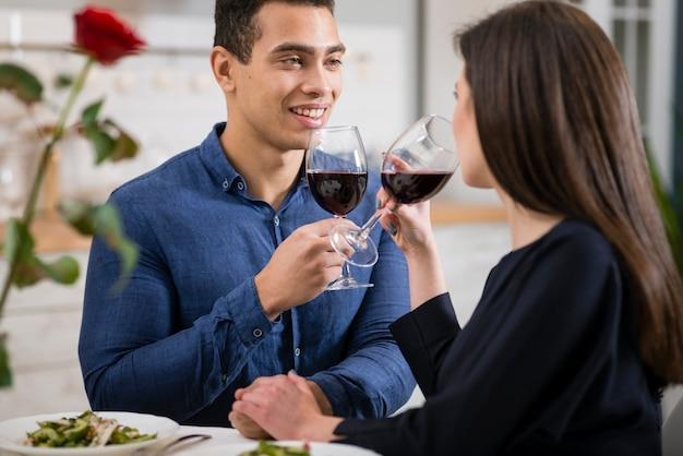 Equipaggi l'esame di sua moglie mentre tengono un bicchiere di vino