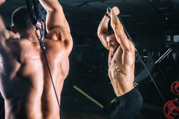 Equipaggi l'esercizio in istruttore per i muscoli del tricipite nella palestra