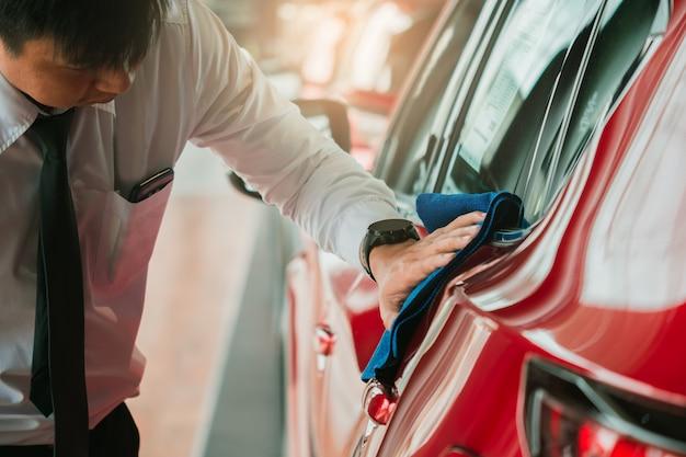 Equipaggi l'ispezione asiatica e l'autolavaggio dell'attrezzatura di pulizia con l'automobile rossa per la pulizia alla qualità al cliente sullo showroom dell'automobile di trasporto di servizio immagine automobilistica del trasporto dell'automobile.