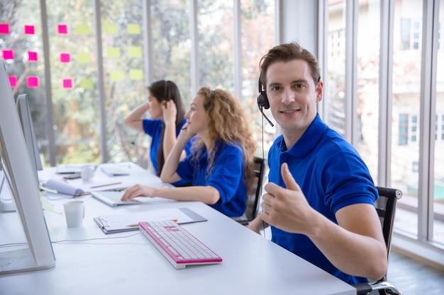 Equipaggi l'operatore che si siede i pollici su ad uno scrittorio davanti al computer