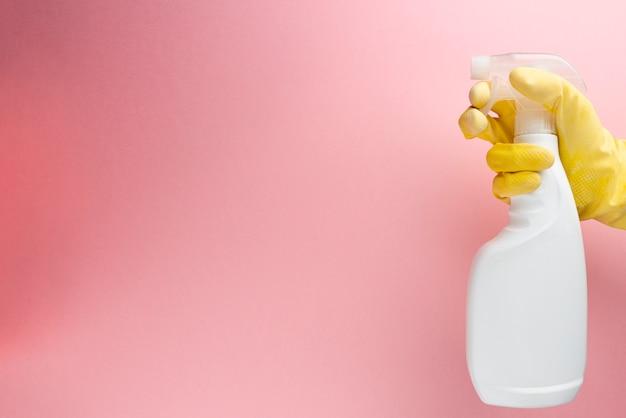 Equipaggi la bottiglia dello spruzzo della tenuta del prodotto di pulizia sopra la parete rosa.