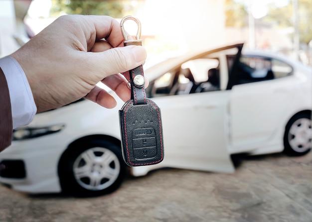 Equipaggi la chiave dell'automobile della tenuta con l'immagine di sfuocatura dell'automobile bianca