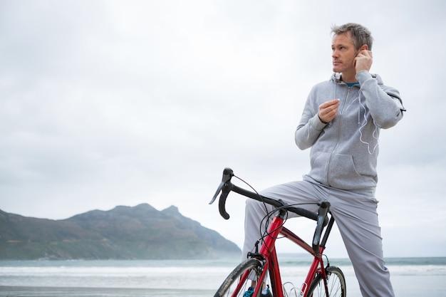 Equipaggi la condizione con la musica d'ascolto della bicicletta sulle cuffie alla spiaggia