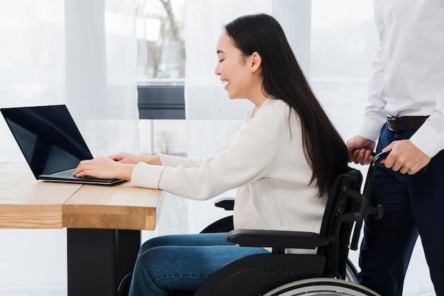 Equipaggi la condizione dietro la donna disattivata sorridente che si siede sulla sedia a rotelle facendo uso del computer portatile