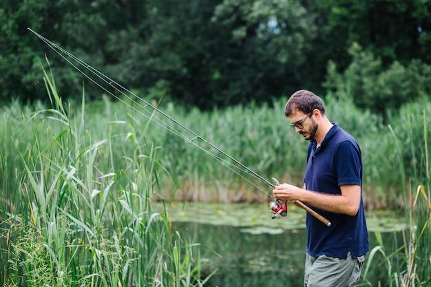 Equipaggi la condizione nello stagno che lega l'amo da pesca