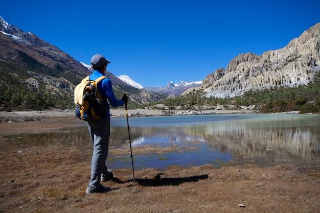 Equipaggi la condizione per guardare la vista del lago con le montagne della neve