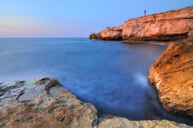 Equipaggi la condizione sulla roccia sopra la linea costiera del mar nero con chiare acque e cielo blu blu