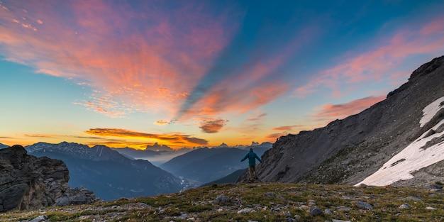 Equipaggi la condizione sulle armi alzanti superiori della montagna, paesaggio variopinto leggero di scenis del cielo dell'alba.