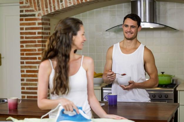 Equipaggi la conversazione con donna mentre mangiano la prima colazione in cucina